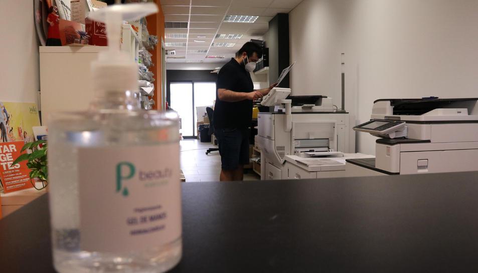 Un empresari autònom d'arts gràfiques treballant amb mascareta, amb una ampolla de gel hidroalcòholic desenfocada en primer pla