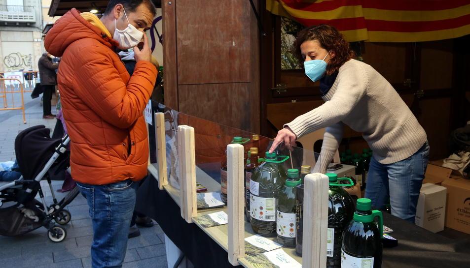 Un comprador i d'una venedora en un dels estands que ha participat en la 20a edició de la fira de l'oli nou DOP Siurana que s'ha celebrat a Tarragona