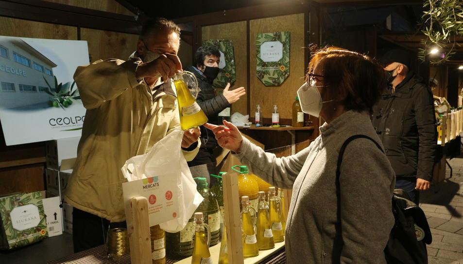 Un comprador mostrant una botella d'oli a una dona en la fira de l'oli nou DOP Siurana que s'ha celebrat a Tarragona
