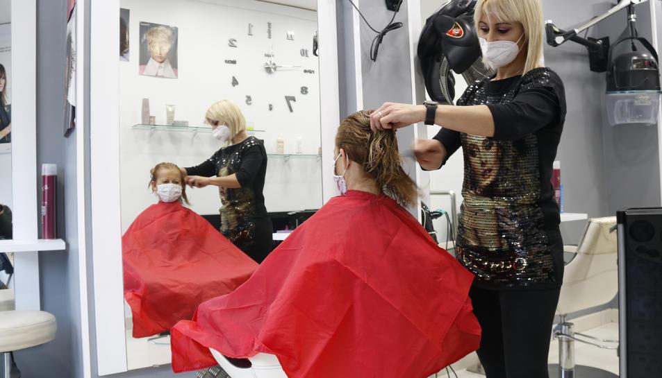 Una perruquera pentinant una clienta a Valls, a les portes del Nadal