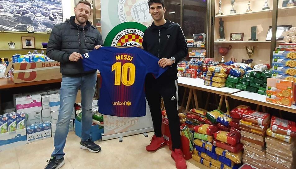 El president de l'associació, Luis Trinidad, i Dídac Gómez, amb la samarreta entregada per Messi