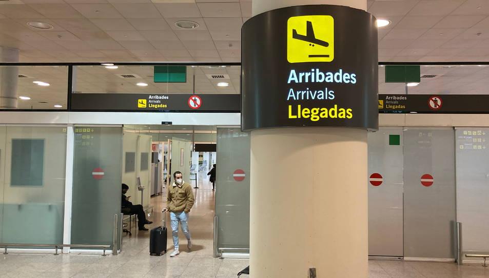 Un senyal de la zona d'Arribades amb un passatger arrossegant una maleta de fons a l'Aeroport del Prat.