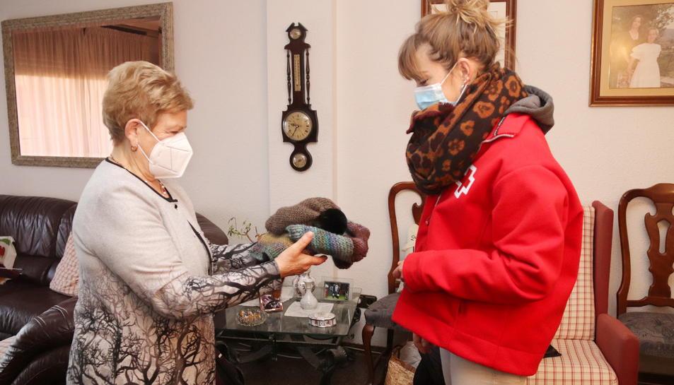 Agapita Hernando, una de les àvies que participa en el projecte de Creu Roja Tarragona, entregant-li una peça de roba que ha teixit a Anna Garrido, tècnica de l'entitat.