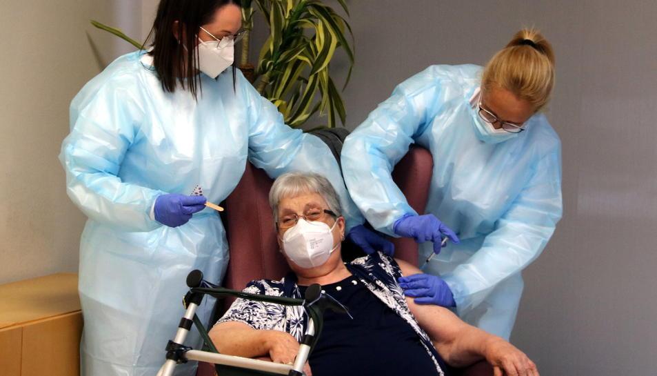 Dues infermeres vacunant contra la covid-19 a Antònia Sedó, usuària de la Residència Natzaret de Móra d'Ebre que ha estat la primera vacunada a la regió sanitària de les Terres de l'Ebre