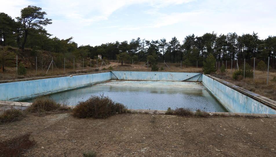 La piscina, mig buida d'aigua i degradada, de l'antic campament militar.