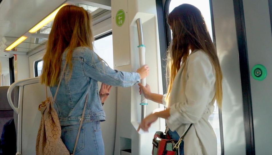 Pla mitja de dues noies agafant-se a la subjecció del tren amb l'escut de mans.
