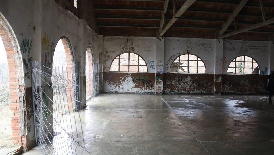 Interior d'una de les naus abandonades de l'antic campament militar.