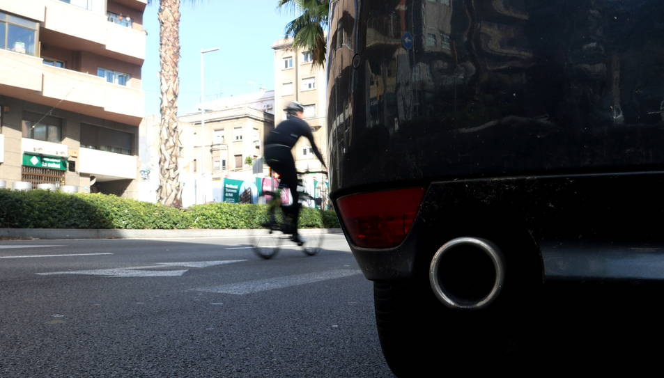 Detall del tub d'escapament d'un cotxe a la Ronda del Mig, i en segon terme una bicicleta passant de llarg.