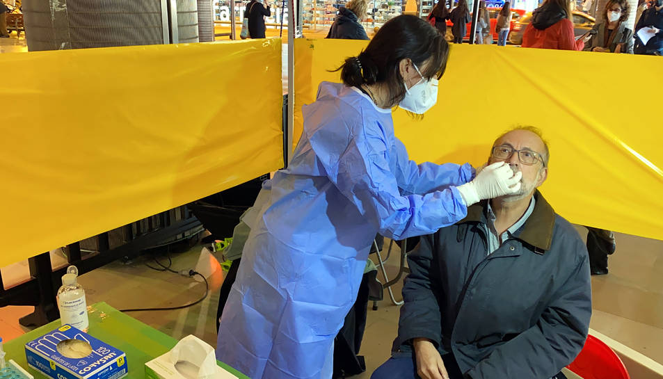 Una persona fent un test ràpid d'antígens en un punt de cribratge.