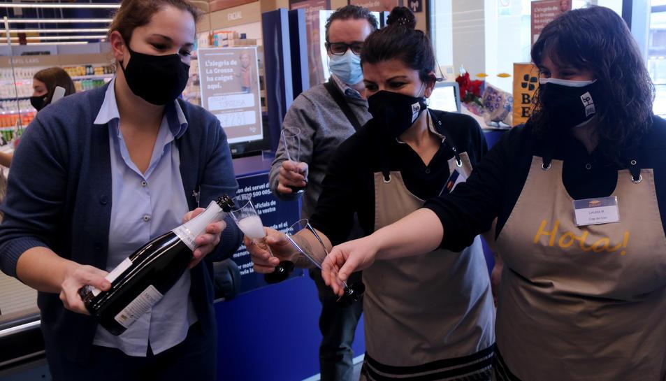 Pla conjunt d'un grup de treballadores del supermercat Bonpreu i Esclat de Tortosa celebrant el tercer premi de la Grossa de Cap d'Any.