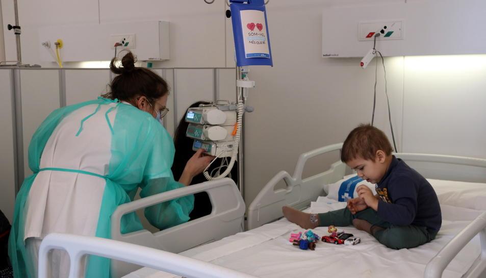 Una infermera supervisa la medicació a un nen a l'Hospital de Dia d'oncologia pediàtrica, on es pot veure la capsa de la medicació amb una il·lustració.