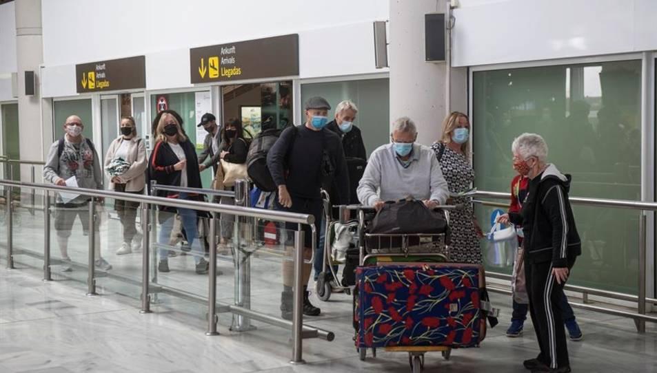 Diversos turistes surten de la sala de recollida d'equipatges a la seva arribada a l'aeroport César Manrique de Lanzarote.
