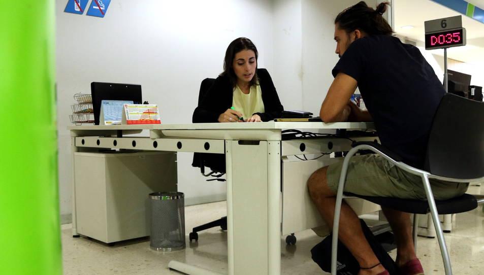Un ciutadà atén les explicacions d'una treballadora del Servei d'Ocupació de Catalunya.