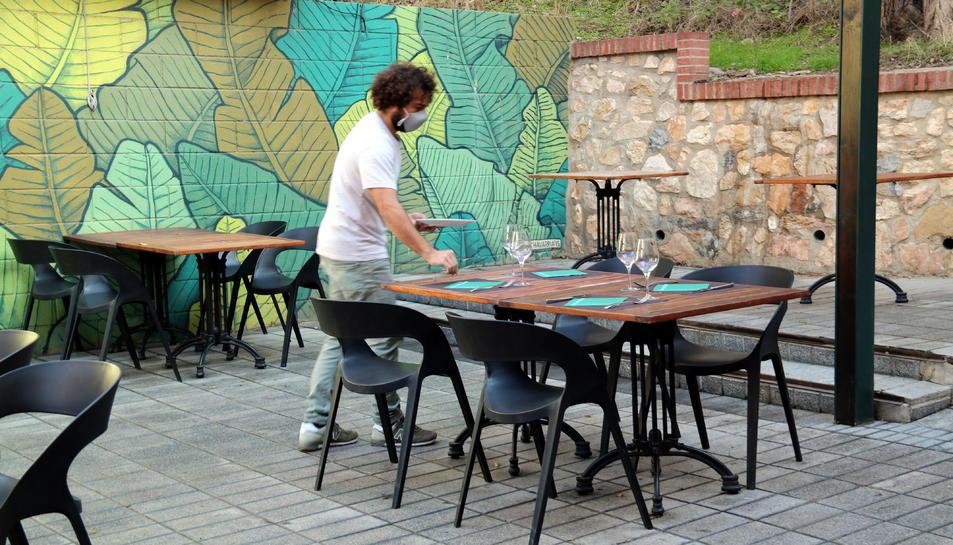 Pla general del copropietari del restaurant Botànic de Tortosa parant taules a la terrassa de l'establiment abans de la reobertura del migdia.