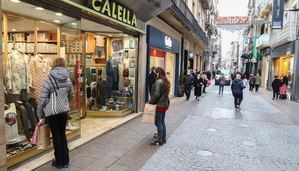 Alguns compradors, ahir al migdia, al carrer Monterols de Reus.