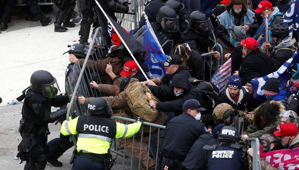La policia intentant contenir els manifestants pro-Trump a l'exterior de l'edifici del Capitoli dels Estats Units.