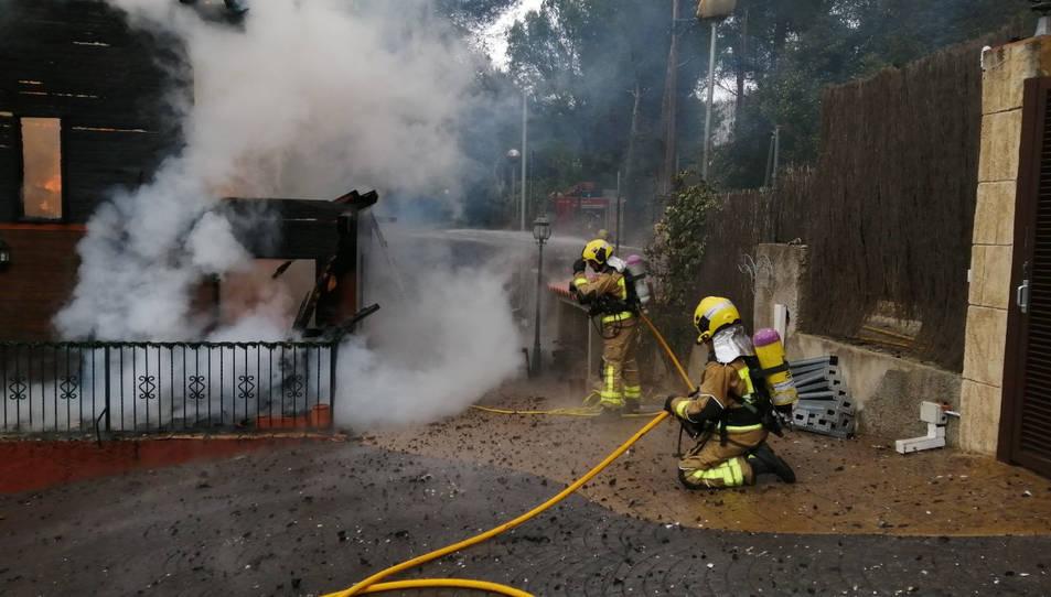 Dos bombers treballant en l'extinció del foc.