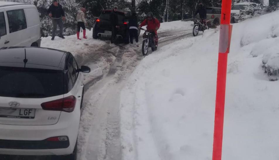 Vehicles fora de la via a l'accés a Prades des d'una màquina llevaneu de la Diputació.