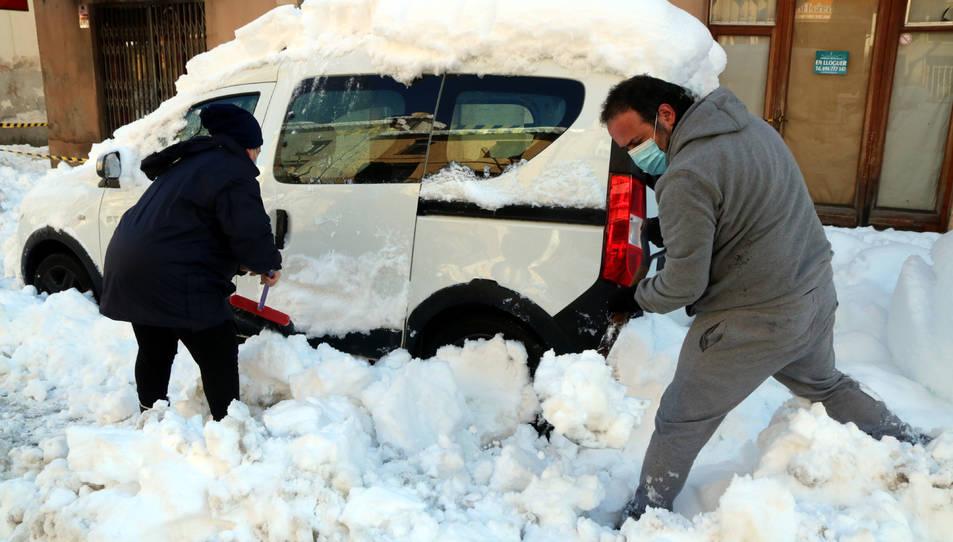 Dos veïns de Falset desenterrant el seu vehicle, colgat per la neu.
