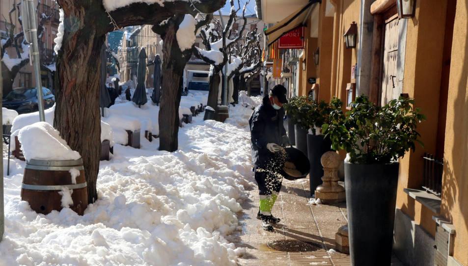 Pla obert d'un efectiu de la brigada muniicpal de Falset espargint sal en un cèntric carrer de la capital del Priorat