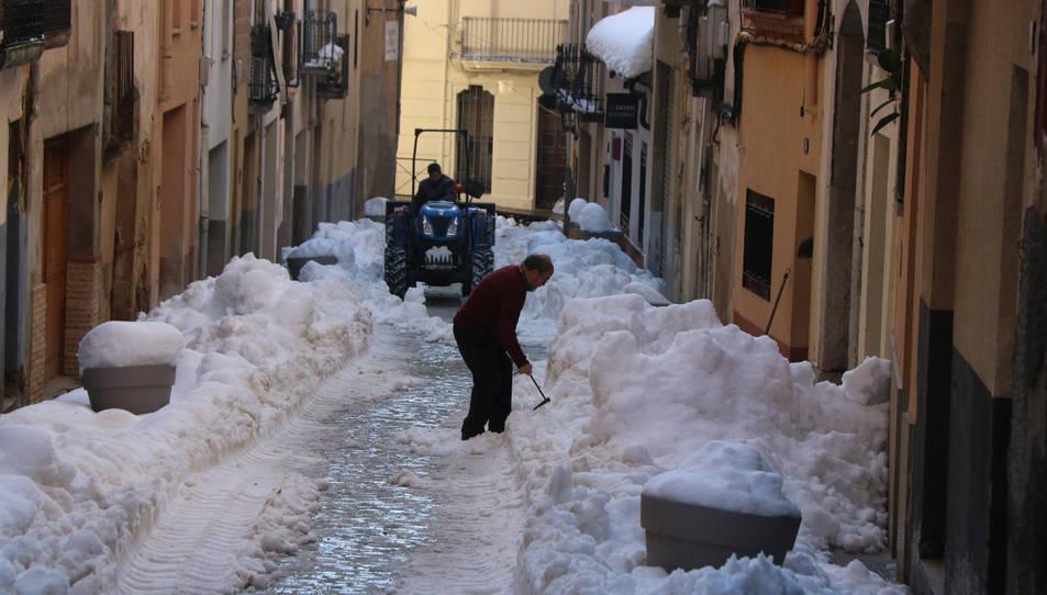 Un carrer de Falset nevat amb un veí retirant neu de la porta de casa seva i un tractor netejant.
