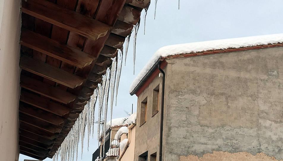 Primer pla dels canelobres de gel penjat d'una teulada a Arnes a primera hora del matí.