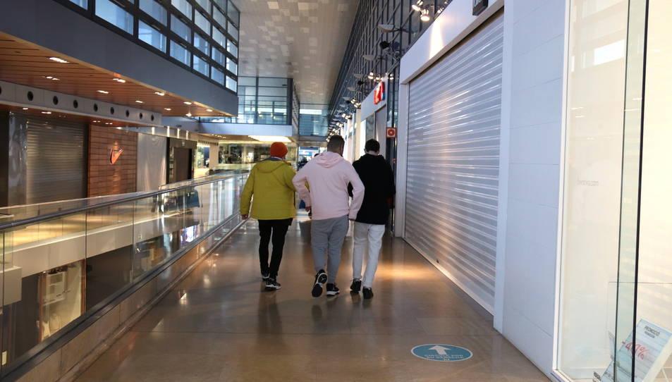 Un grup de joves caminant dins del centre comercial L'Illa Diagonal amb totes les botigues tancades.