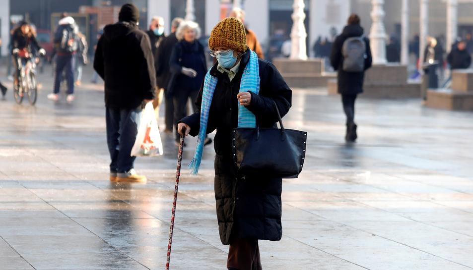 Una dona caminant amb mascareta.