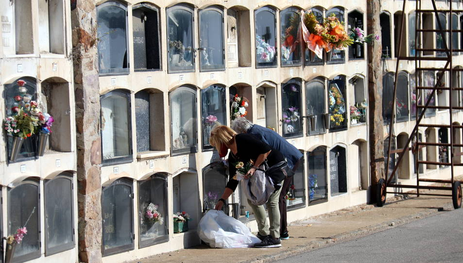 Dues dones dipositen flors en una tomba al cementiri de Montjuïc per Tots Sants
