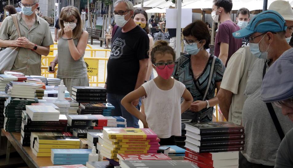 Compradors amb mascaretes mirant llibres al Sant Jordi d'estiu de Girona.