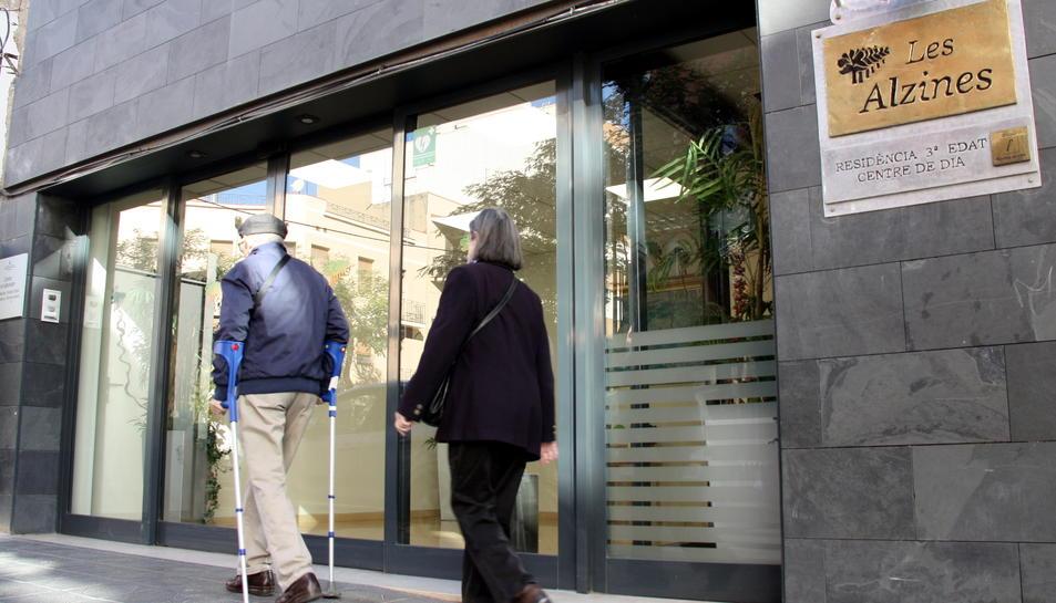 Façana principal de la residència Les Alzines de Tarragona, i d'una parella d'avis a punt d'entrar-hi