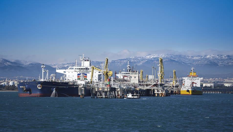 Imatge de diversos vaixells atracats al pantalà de Repsol al Port de Tarragona, amb muntanyes enfarinades al fons.