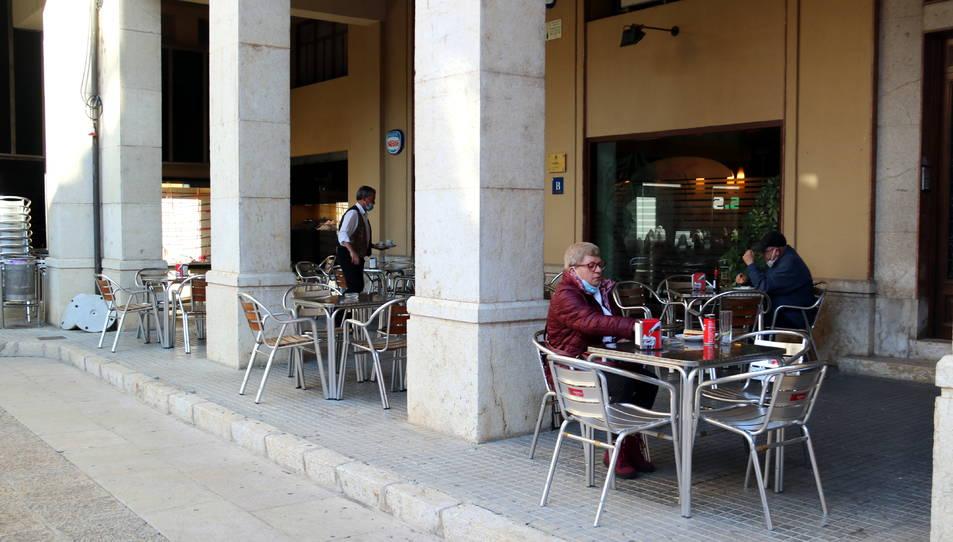 Ls terrassa del bar La Tertúlia de Tortosa amb alguns clients i el seu propietari servint-los.