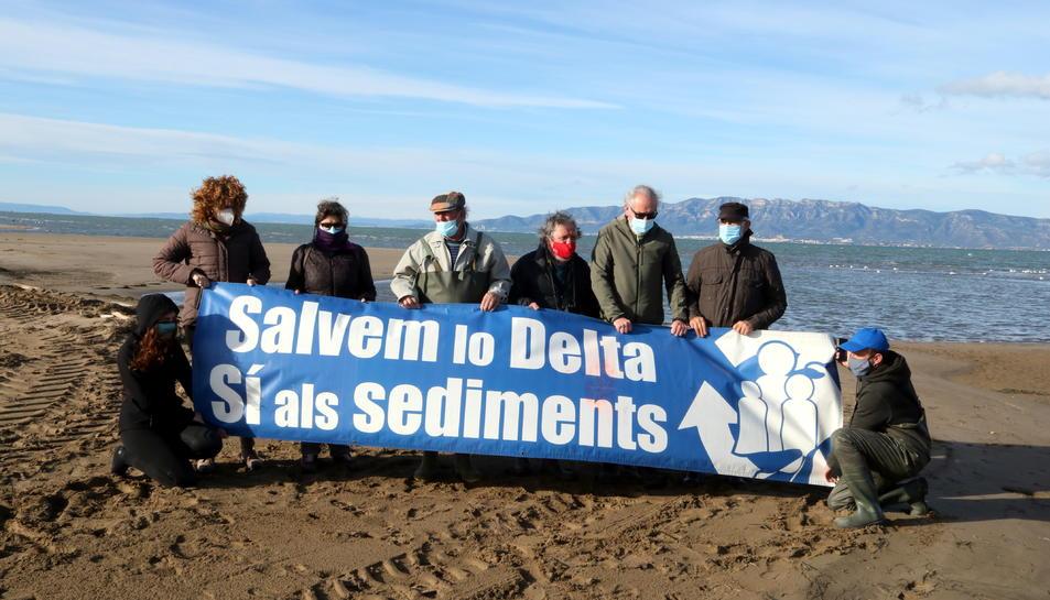 Activistes de l'Associació Sediments amb una pancarta reivindicativa abans de començar l'acció visual per denunciar la fragilitat de la barra del Trabucador.