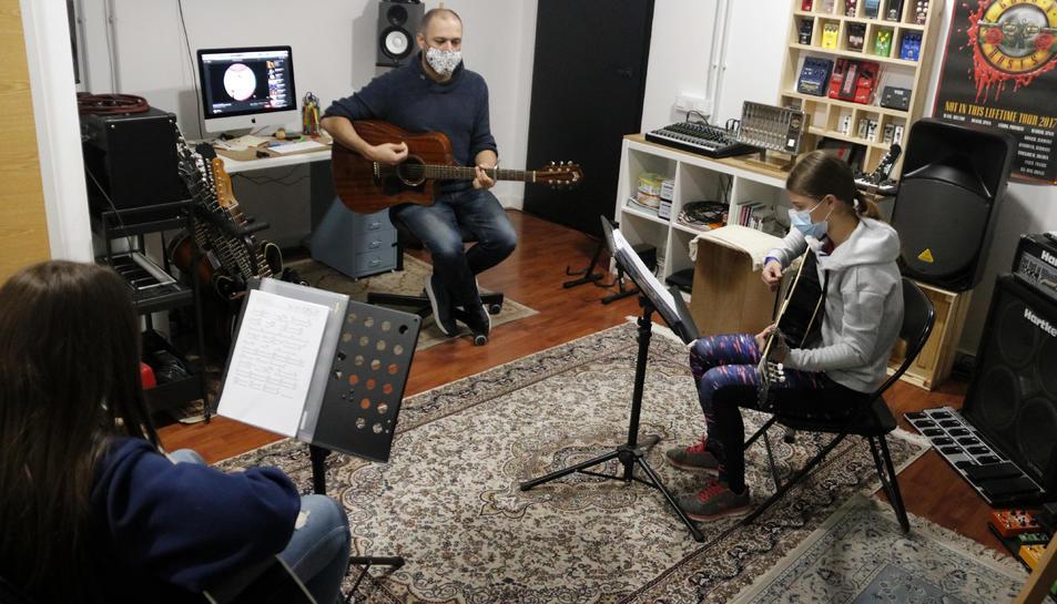 Albert Gilabert, professor de guitarra de l'aula El Traster de Mollerussa, fent classe amb dos alumnes, en la represa de les activitats extraescolars.