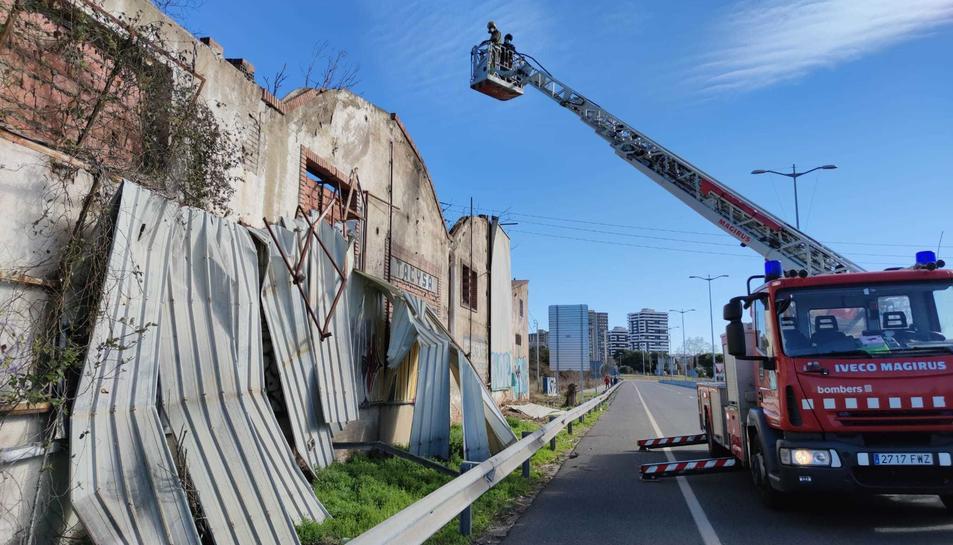 Els Bombers treballant per retirar ls planxes metàliques que obstaculitzaben la via.
