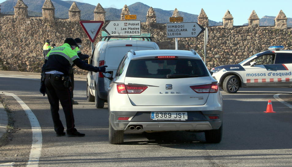 Agents de Mossos d'Esquadra aturant dos vehicles al control policial fet a la carretera T-700 al terme municipal de Vimbodí i Poblet.