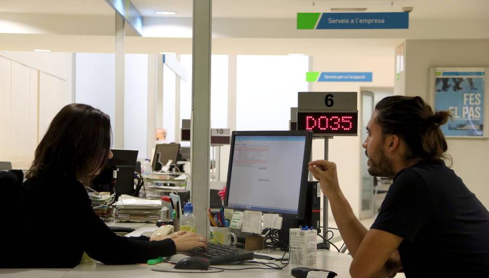 Una treballadora del SOC i un home conversen en un dels punts d'atenció del Servei d'Ocupació de Catalunya.