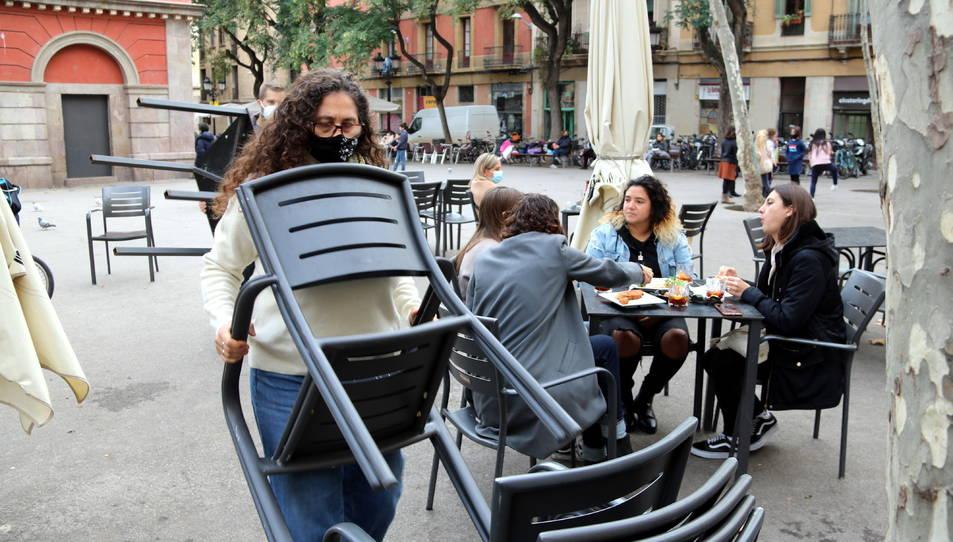 Treballadors del restaurant Amélie de la plaça de la Vila recollint taules i cadires amb gent encara menjant, e