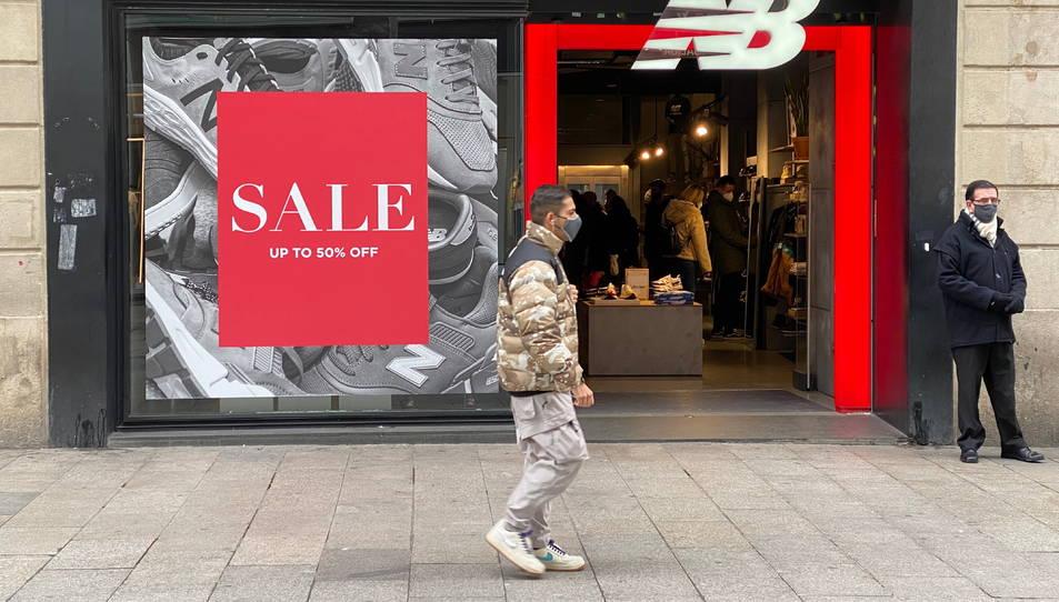 Un comprador davant d'una botiga de roba oberta al Portal de l'Àngel en el primer dia de rebaixes.
