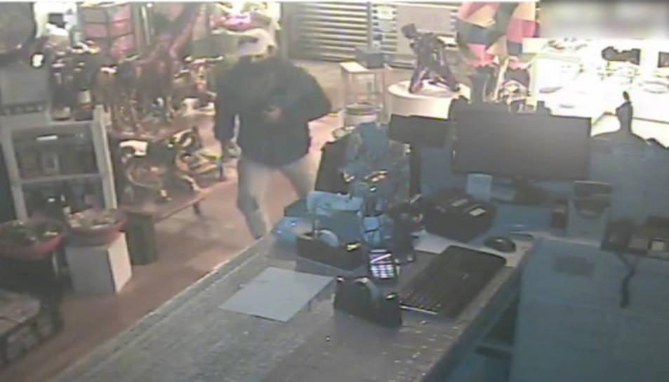 Pla general de la imatge enregistrada per la càmera de seguretat d'un establiment, on es pot veure el lladre.