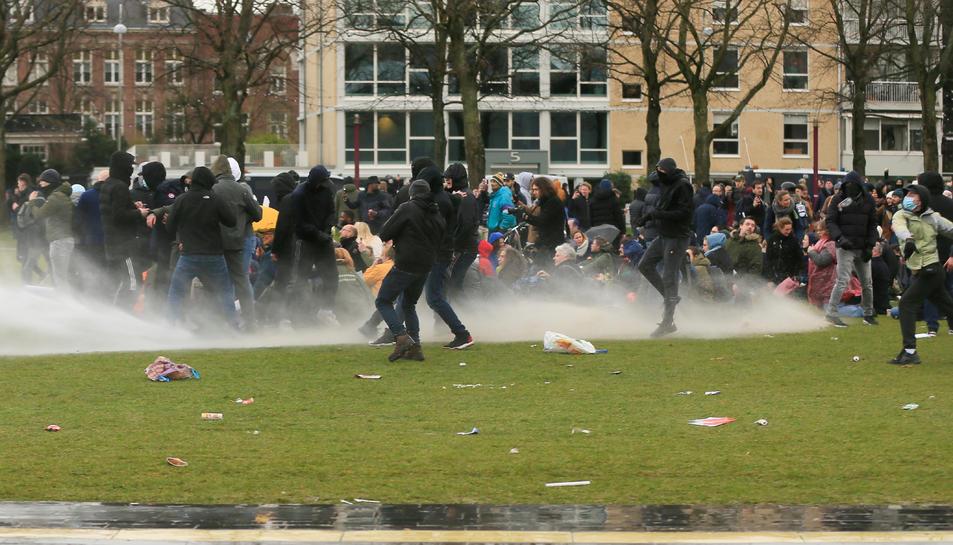 La policia utilitza un canó d'aigua durant una protesta contra les restriccions establertes per frenar la propagació de la malaltia del coronavirus (COVID-19), a Amsterdam.
