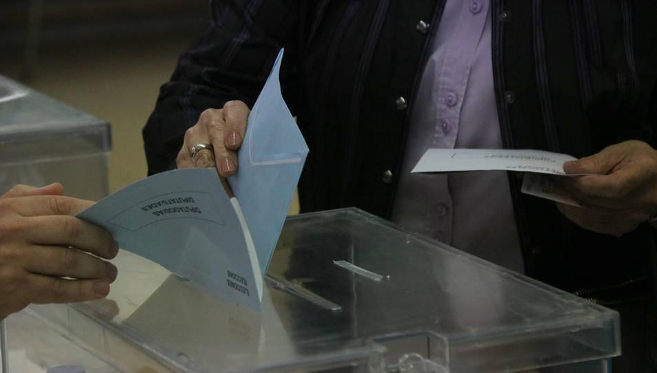 Instant en què una dona diposita el seu vot.