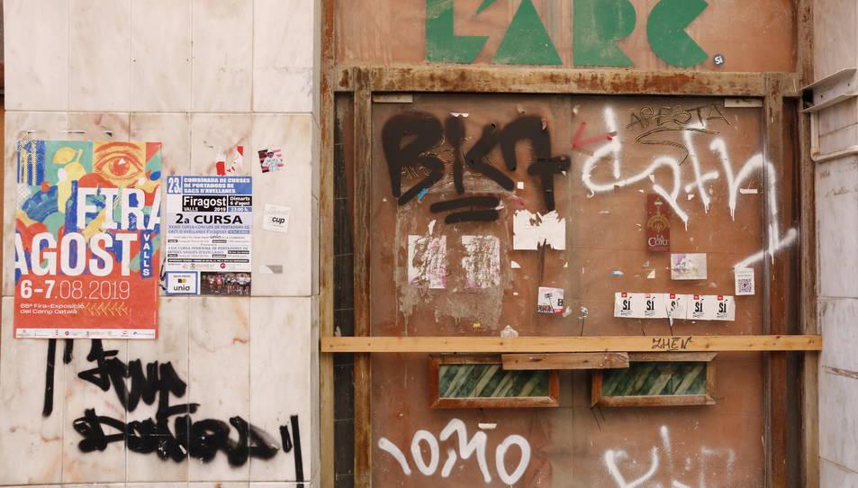 Grafits a la porta d'un antic establiment del carrer de la Cort, situat en un edifici històric conegut com Ca Padró.