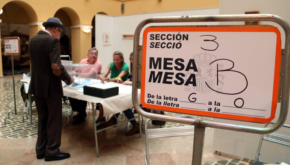 Un cartell indicatiu i d'un elector votant en un dels col·legis electorals de la ciutat de Tarragona.