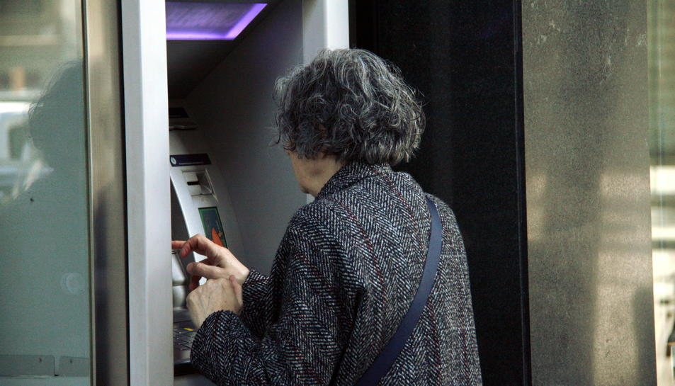 Imatge d'arxiu d'una persona utilitzant un caixer automàtic.