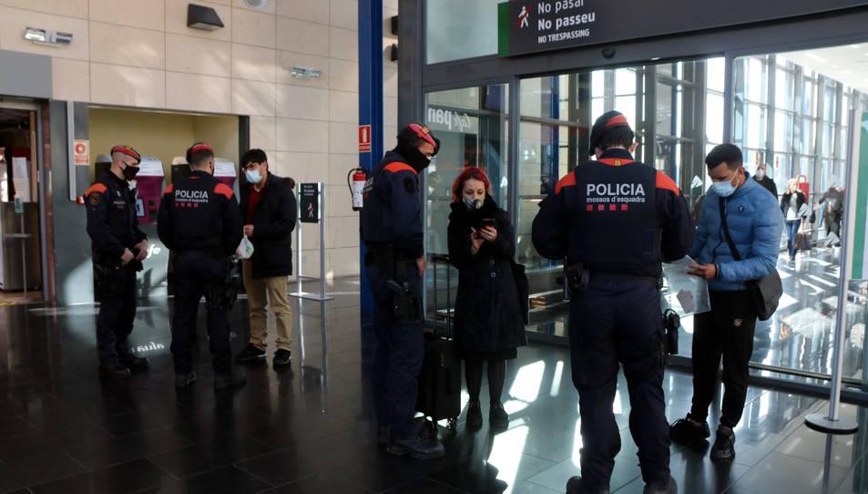 Diversos viatgers de l'AVE mostrant certificats de desplaçament a agents dels Mossos d'Esquadra durant un control de mobilitat.