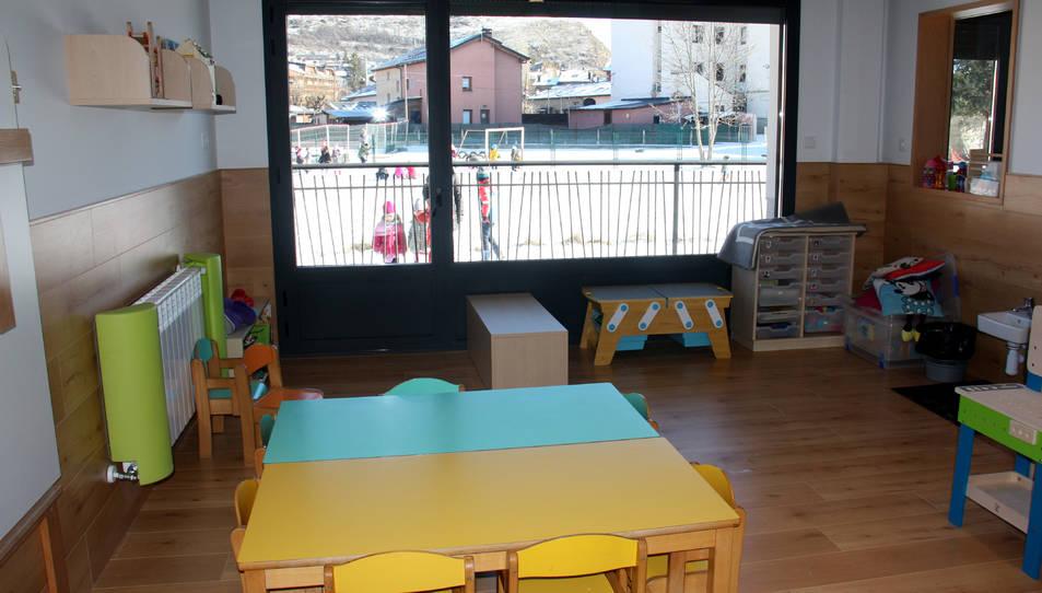 Una aula d'una llar d'infants on es veuen alumnes al pati.