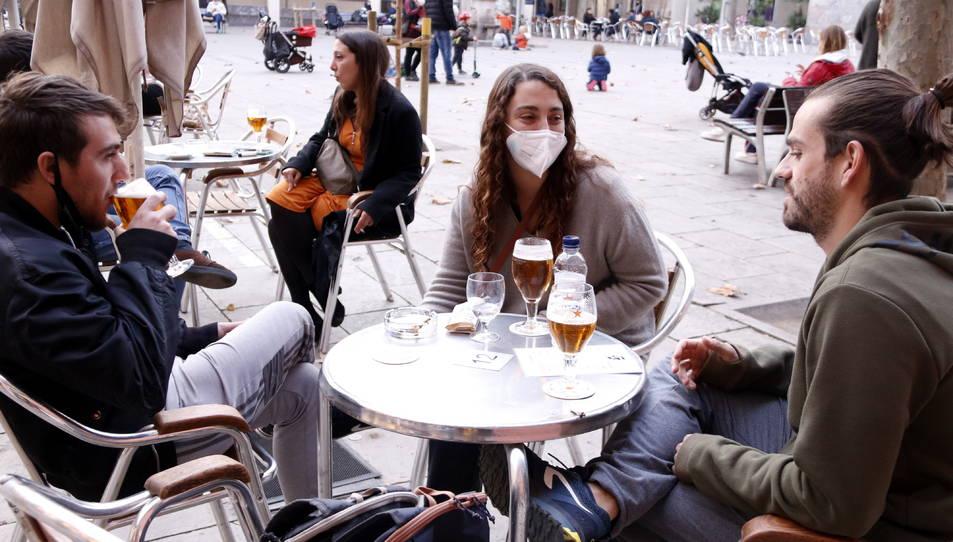 Uns joves prenen una cervesa en una terrassa a la plaça de la Virreina.
