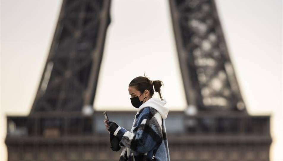 Una dona amb mascareta passant davant de la Torre Eiffel.
